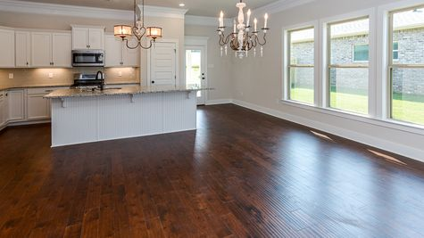 Oldtown II D - Open Floor Plan - DSLD Homes - Kitchen with white cabinets, wood floors, and stainless appliances