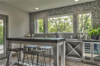Wet Bar Features Tiled Wall with Lower Cabinets with Glass Doors, Built in Wine Rack, Space for Under Cabinet Beverage Fridge, Tiled Floor and Access to the Covered Deck which is great for entertaining on the Private Wooded Lot. Picture is of Actual Home.